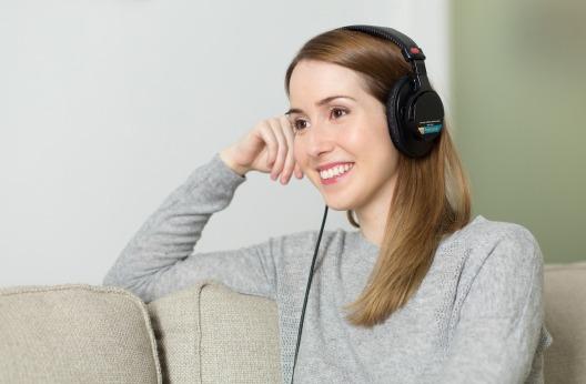 Mujer escuchando la radio con su dispositivo móvil.